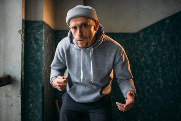 Агрессивный грабитель с ножом вселяет страх. уличный бандит ждет жертву. понятие преступления, опасность нападения грабежа