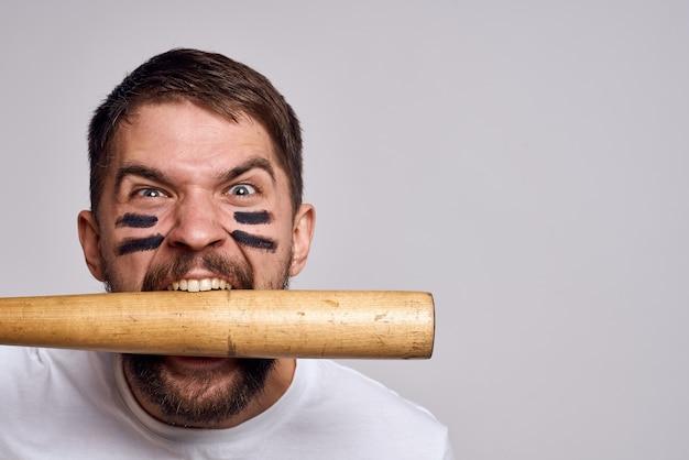 Aggressive man biting from a baseball bat