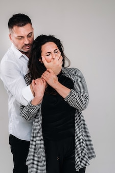 An aggressive man covers the mouth of a beaten woman so that she cannot scream. domestic violence.