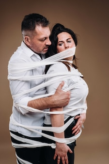 An aggressive man embraces a battered woman and is wrapped in bandages together. domestic violence.