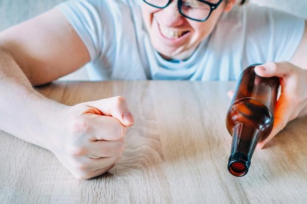 Агрессивный мужчина бьет по столу