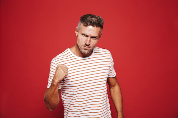 Aggressive man in striped t-shirt looking with loathing and showing fist isolated on red