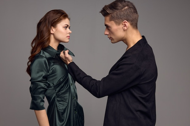 Aggressive man in a suit holds a woman by the collar of a dress on a gray background. high quality photo