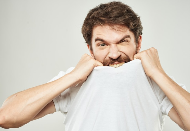 Aggressive man in a white t-shirt irritability emotions light background. high quality photo