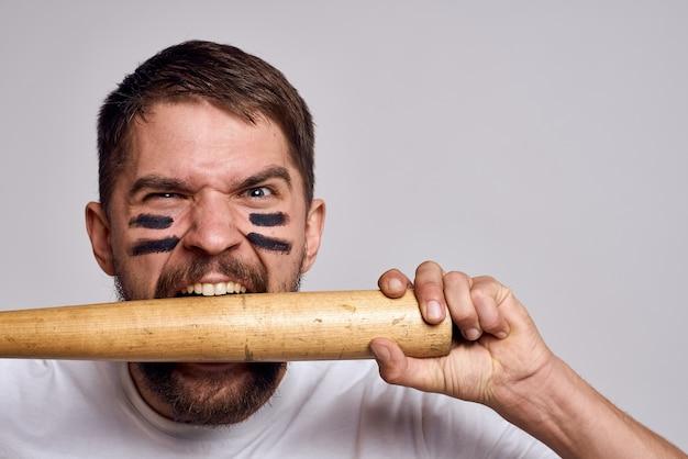 Агрессивный мужчина с бейсбольной битой в руках на сером