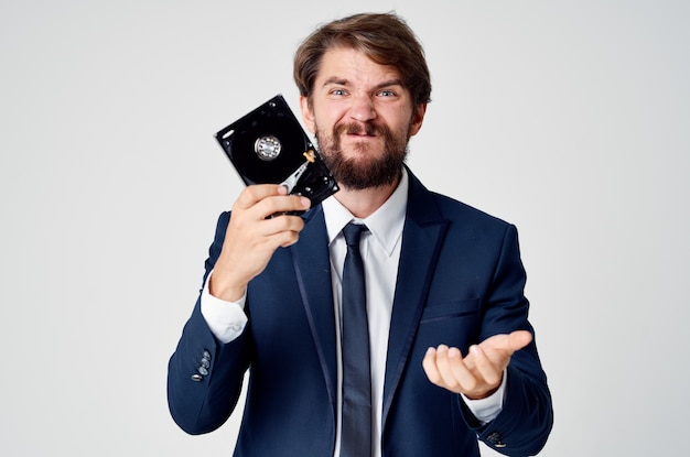 Aggressive man with hard drive in hands emotions irritability light background business finance. high quality photo