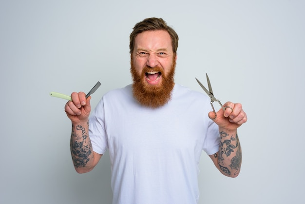 Aggressive man with scissors and blade is ready to cut the beard