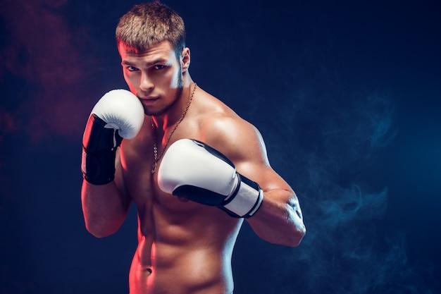 Агрессивный боксер без рубашки на сером фоне.