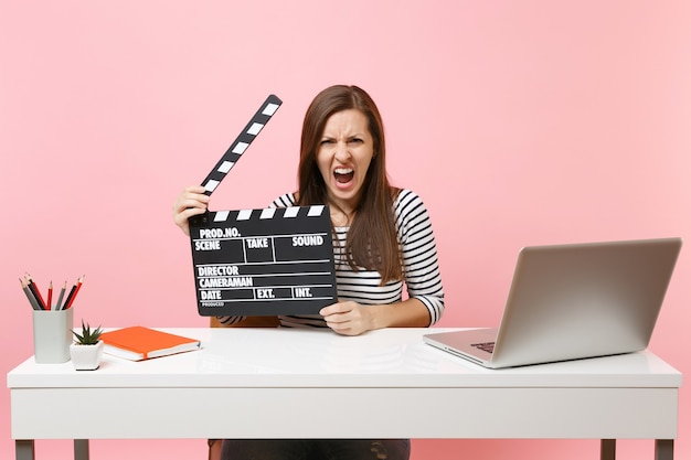 Aggressive woman screaming holding classic black film making clapperboard and working on project while sit at office with laptop isolated on pink background. achievement business career. copy space.