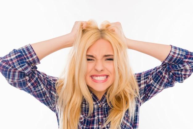 Агрессивная молодая блондинка держит голову и показывает зубы