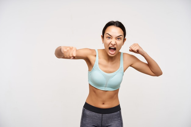 Aggressive young brown haired woman with casual hairstyle boxing with raised fists and grimacing her face while screaming furiously, posing over white wall