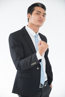 Aggressive young businessman threatening with fist