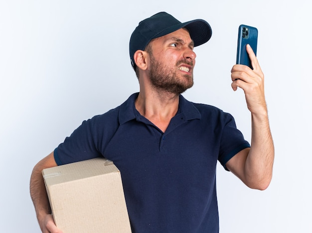 Aggressive young caucasian delivery man in blue uniform and cap holding cardboard box and mobile phone looking at phone isolated on white wall
