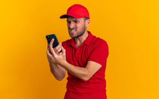 빨간색 유니폼을 입은 공격적인 백인 배달원과 프로필 보기에 서 있는 모자는 복사 공간이 있는 주황색 벽에 격리된 휴대 전화를 들고 보고 있습니다. 무료 사진
