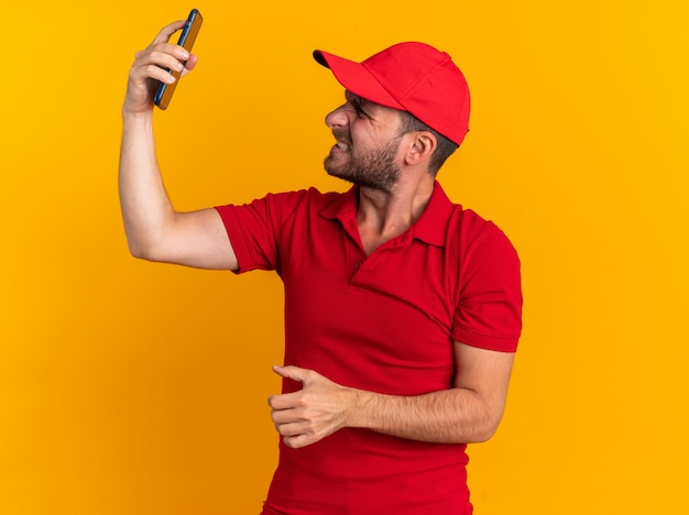 Aggressive young caucasian delivery man in red uniform and cap raising and looking at mobile phone isolated on orange wall