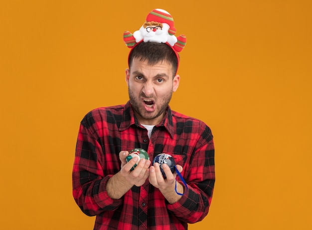 Агрессивный молодой кавказский мужчина в повязке на голову санта-клауса смотрит в камеру с рождественскими шарами, изолированными на оранжевом фоне