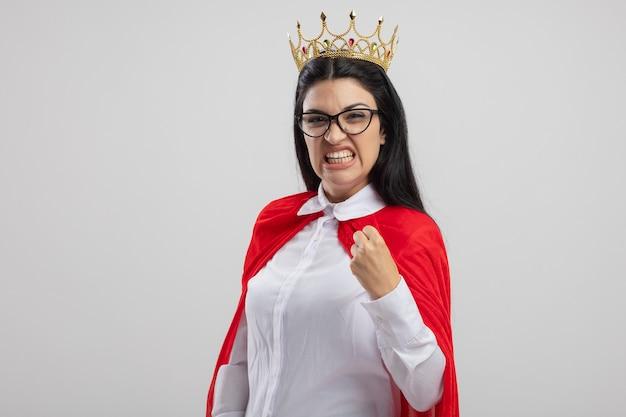 Агрессивная молодая кавказская девушка-супергерой в очках и короне, смотрящая на камеру, сжимая кулак, изолированную на белом фоне с копией пространства