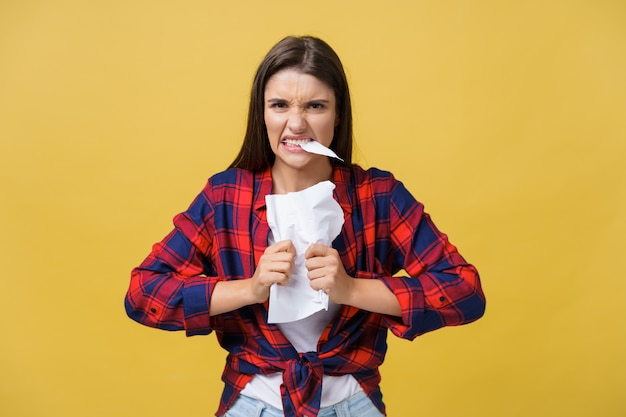 Aggressive young caucasian woman tears contract or white sheet of paper.