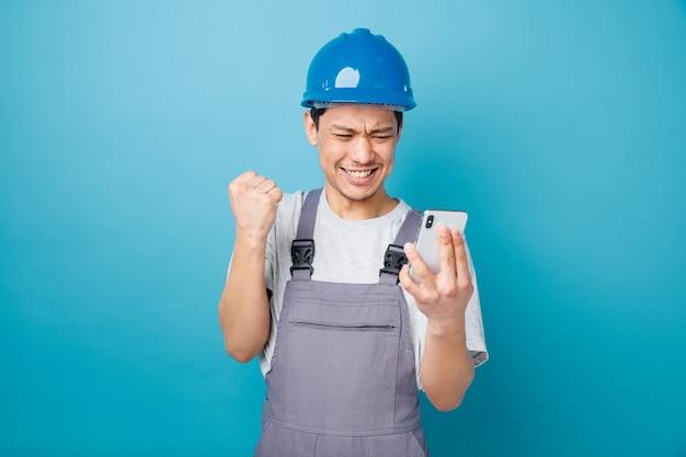 Giovane operaio edile aggressivo che indossa il casco di sicurezza e che tiene uniforme e che esamina il telefono cellulare che fa il gesto di sì