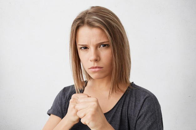 不正行為や暴力から身を守るために拳を準備する攻撃的な若い女性。ボクシングのように拳を握りしめ、強い表情で見ている強い女性