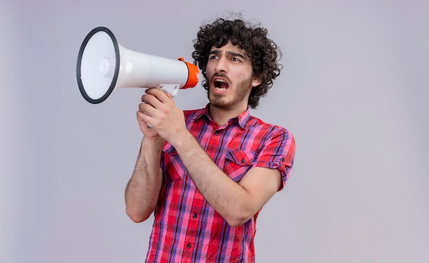 An aggressive young handsome man with curly hair in checked shirt holding megaphone and wanting to say something