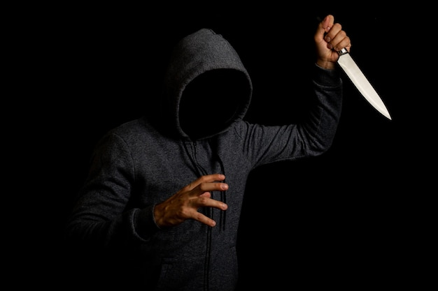 Aggressive young man in a hoodie holding a knife