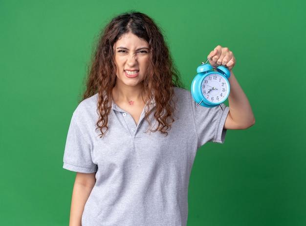 Агрессивная молодая симпатичная кавказская девушка держит будильник