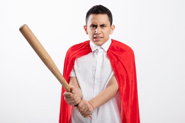복사 공간 흰색 배경에 고립 된 카메라를보고 야구 방망이 들고 빨간 케이프에서 적극적인 젊은 슈퍼 히어로 소년