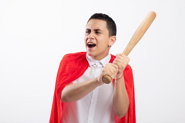 Ragazzo aggressivo del supereroe giovane in mantello rosso che tiene la mazza da baseball guardando il lato sempre pronto a colpire isolato su sfondo bianco con spazio di copia