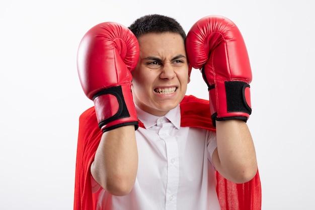 Ragazzo aggressivo giovane supereroe in mantello rosso che indossa i guanti di scatola guardando dritto tenendo le mani sulla testa isolato su sfondo bianco