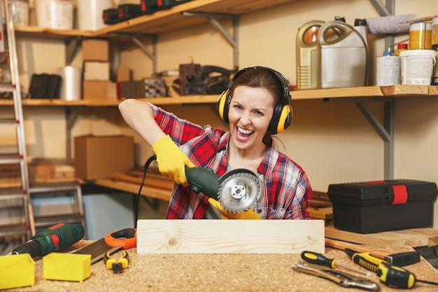 格子縞のシャツ、灰色のtシャツ、遮音ヘッドフォン、さまざまなツールを使用して木製のテーブルの場所で大工仕事のワークショップで作業している黄色の手袋、パワーソーで木材を鋸で挽く積極的な若い女性。