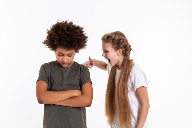 Агрессивно кричать. сумасшедшая выразительная маленькая девочка трогает своего увядшего темноволосого друга и кричит на него