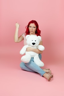 An aggrieved, humiliated woman holds a large white teddy bear and shakes her fist