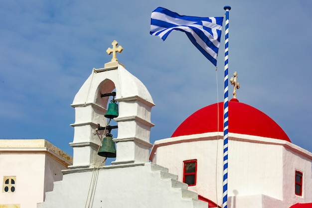 Церковь агиа кириаки, типичное греческое церковное белое здание с красным куполом и большим развевающимся греческим флагом на фоне голубого неба на острове миконос, греция