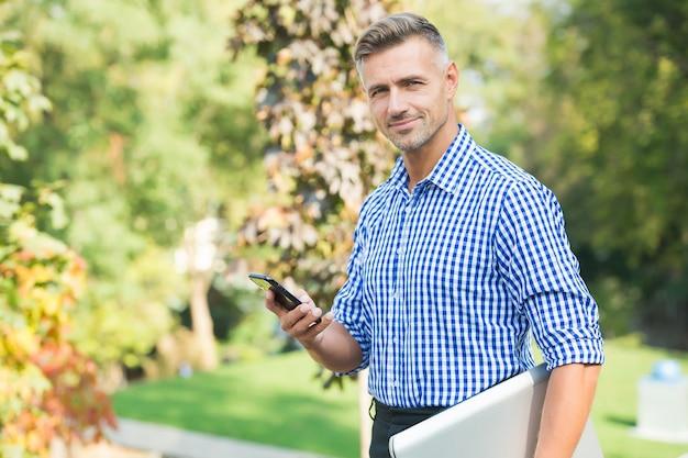 アジャイルビジネス。最新のデバイスとの通信。常にオンラインを維持します。陽気な男は携帯電話で話します。ハンサムなビジネスマンは白髪を手入れしました。成熟した男はコンピュータを運ぶ。