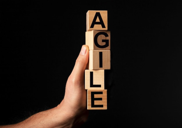 Agile word on wooden blocks in male hand over black background with copy space for text
