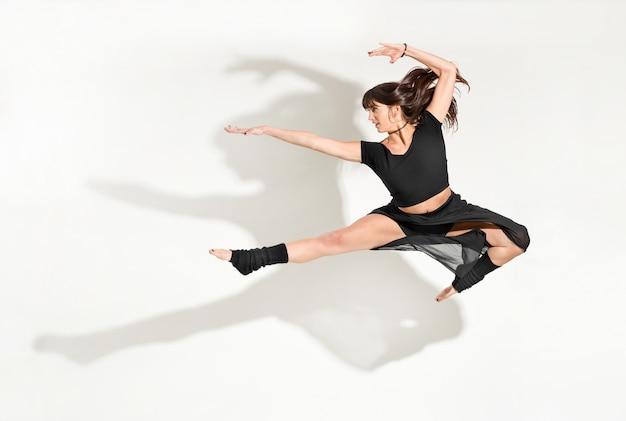 Гибкая молодая женщина-танцовщица, выполняющая прыжок вперед половину шпагата с длинными волосами, развевающимися в воздухе, изолирована на белом фоне с драматической тенью и пространством