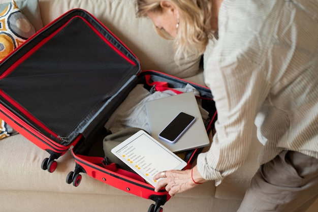Aging female looking through travel list in digital tablet while sitting on the floor and bending over open suitcase with clothes and gadgets