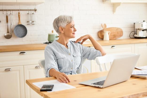 老化、人と技術の概念。開いたラップトップ、電卓、書類、国内予算を管理するキッチンテーブルに座っている青いドレスを着た短い髪の年配の女性の屋内ショット