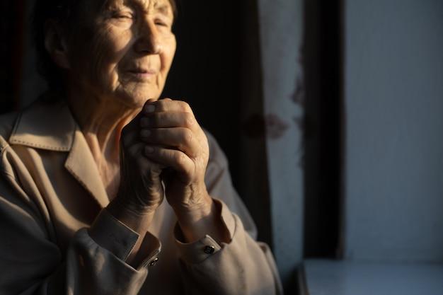 老化プロセス-非常に年配の年配の女性がしわのある肌を手にします