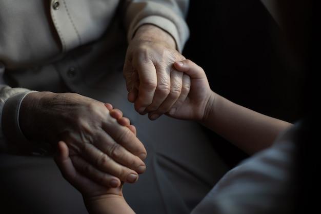 老化の過程-非常に年配の年配の女性がしわのある肌を手にします