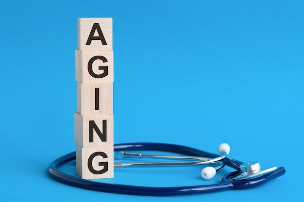 木製のブロックと水色の表面の聴診器に書かれた老化の言葉