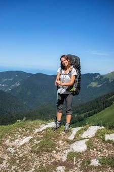 山の中で重いバックパックを持つ少女