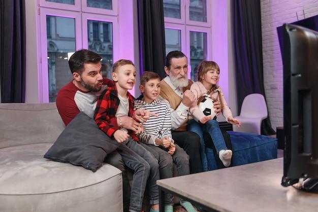 Взволнованные привлекательные три поколения людей, такие как папа, дедушка и внуки, которые все сидят дома на диване