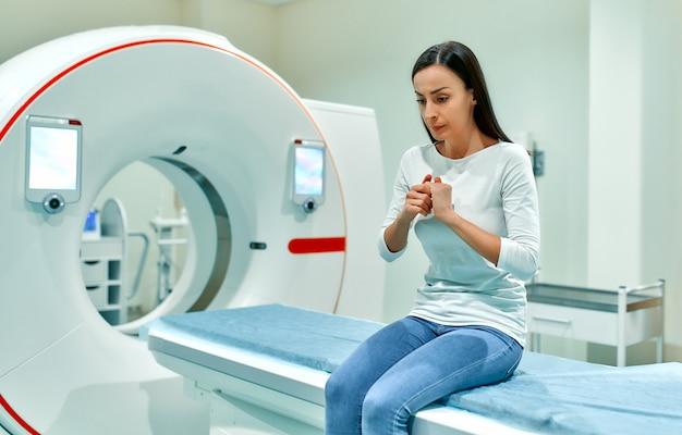 불안하고 슬프고 겁에 질린 환자가 ct 장비의 침대에 앉아 있습니다.