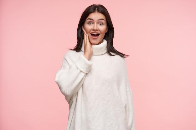 Agitato giovane attraente donna dai capelli castani con acconciatura casual alzando emotivamente la mano al viso mentre guarda sorprendentemente davanti, isolato sopra il muro rosa