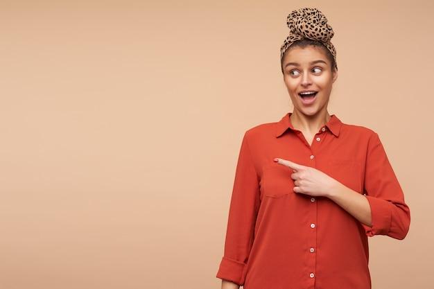 Agitato giovane donna attraente bruna vestita in abiti casual tenendo la bocca spalancata mentre indica eccitato da parte, isolato sul muro beige