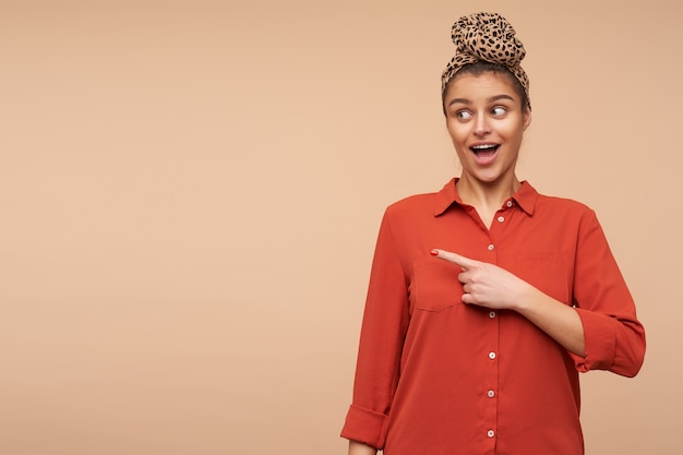 ベージュの壁に隔離され、興奮して脇を指して、口を大きく開いたままカジュアルな服を着た興奮した若い魅力的なブルネットの女性