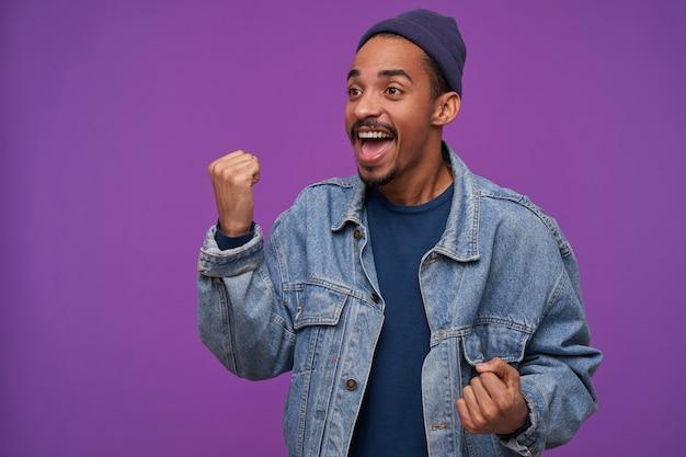 青い帽子とジーンズのコートで興奮した若い魅力的な暗い肌のひげを生やした男は興奮した顔で脇を見て、紫色の壁の上に立って、感情的に彼の拳を上げます