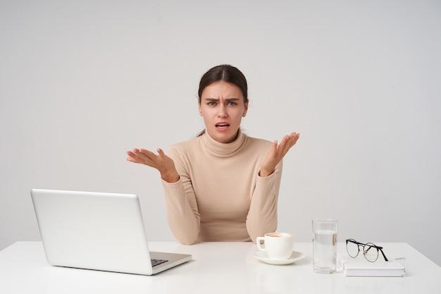 흰 벽 위에 포즈를 취하는 동안 공식적인 옷을 입고 현대 노트북으로 사무실에서 일하면서 카메라를 혼란스럽게 보면서 손을 올리는 흥분된 젊은 아름다운 검은 머리 여성